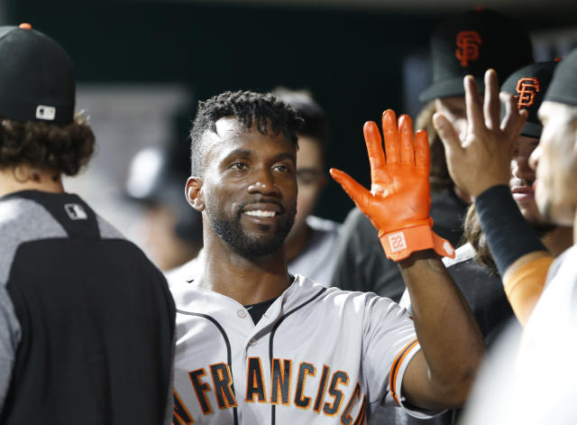 FILE - In this Aug. 18, 2018, file photo, San Francisco Giants' Andrew McCutchen, center, is congratulated in the dugout after scoring during the eighth inning of a baseball game against the Cincinnati Reds, in Cincinnati.The playoff-contending New York Yankees are close to completing a trade for San Francisco Giants outfielder Andrew McCutchen. A person familiar with the negotiations told The Associated Press on Thursday night, Aug. 30, 2018, the Yankees would send infielder Abiatal Avelino and another minor leaguer to San Francisco for McCutchen. The person spoke on condition of anonymity because the deal wasn't finalized. (AP Photo/Gary Landers, File)