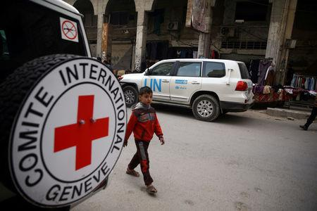 A Syrian child is seen walking near International Red Cross vehicle in the rebel-held city of Douma, in the eastern Damascus suburb of Ghouta, Syria November 12, 2017. REUTERS/Bassam Khabieh