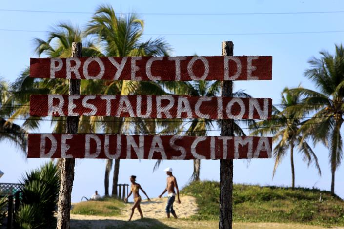 """In this May 24, 2013 photo, people walk on the beach behind a sign that reads in Spanish """"Dune Restoration Project, CITMA"""" in Havana, Cuba. In recent months, inspectors and demolition crews have begun fanning out across the island with plans to raze thousands of houses, restaurants, hotels and improvised docks in a race to restore much of the coast to something approaching its natural state. (AP Photo/Franklin Reyes)"""