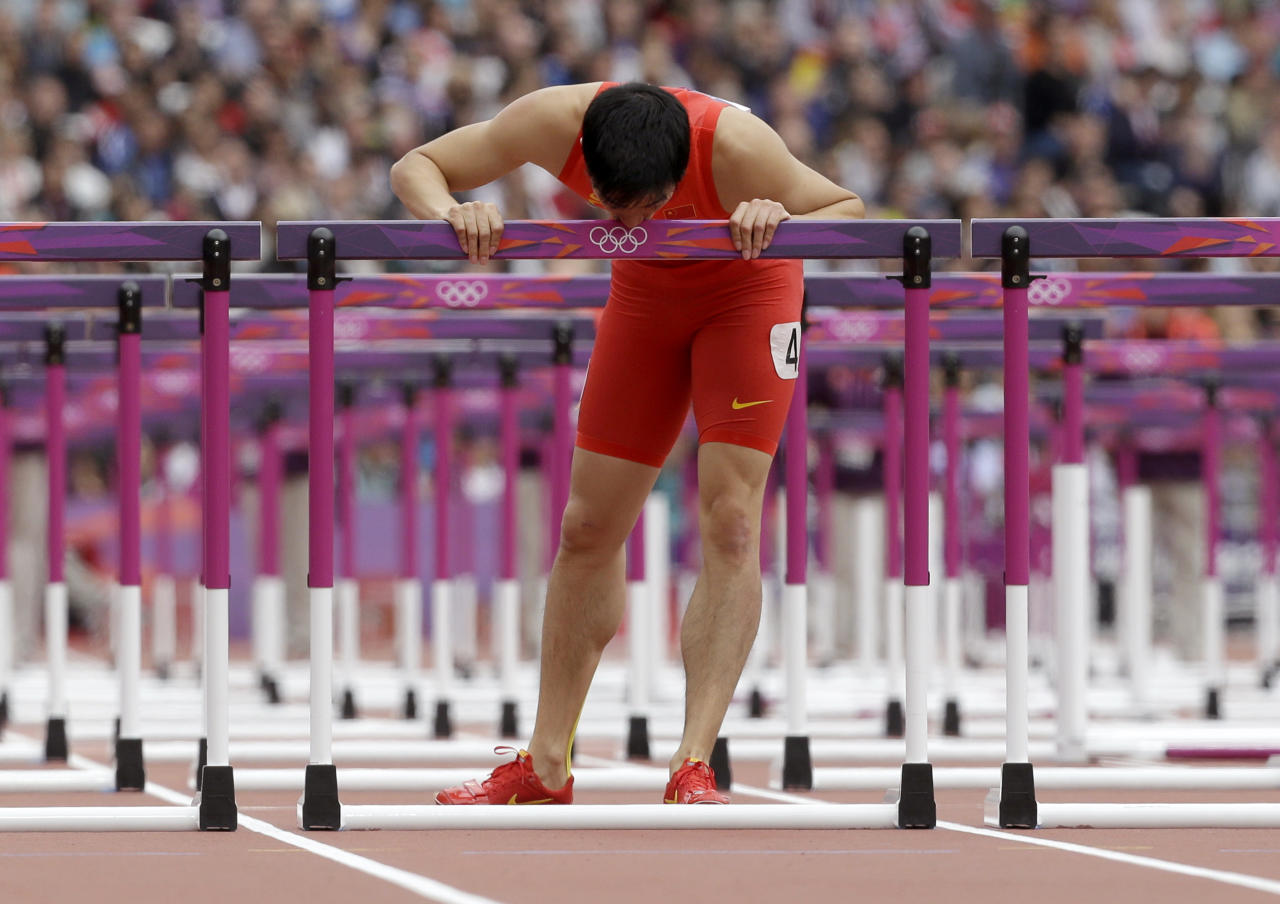 China's Liu Xiang kisses his hurdle after falling in a men's 110-meter hurdles heat during the athletics in the Olympic Stadium at the 2012 Summer Olympics, London, Tuesday, Aug. 7, 2012. (AP Photo/Anja Niedringhaus)