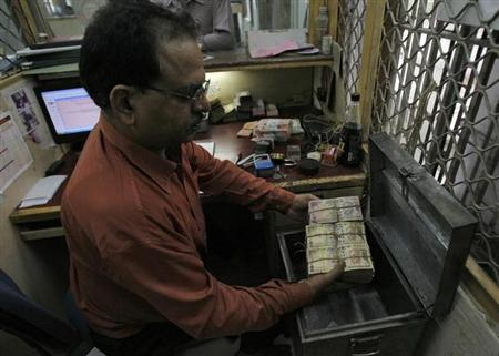 An employee arranges Indian currency notes at a cash counter inside a bank in New Delhi June 8, 2010.An employee arranges Indian currency notes at a cash counter inside a bank in New Delhi June 8, 2010.
