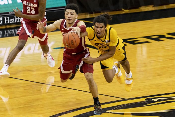 Missouri's Dru Smith, right, and Jahvon Quinerly, left, battle for a loose ball during the second half of an NCAA college basketball game Saturday, Feb. 6, 2021, in Columbia, Mo. Missouri won 68-65. (AP Photo/L.G. Patterson)