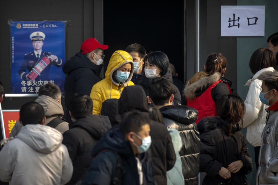 People wearing face masks to protect against the spread of the coronavirus walk out of a site for mass COVID-19 testing in a central district of Beijing, Friday, Jan. 22, 2021. Beijing has ordered fresh rounds of coronavirus testing for about 2 million people in the downtown area following new cases in the Chinese capital. (AP Photo/Mark Schiefelbein)