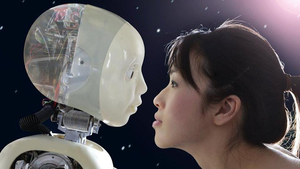 A woman staring into a robot`s eyes