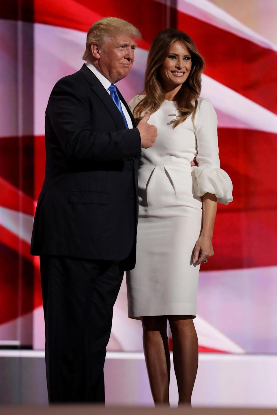 <p>Posing in front of a crowd, Melania stood with her husband in a fitted white dress with ruffled sleeves. <i>[Photo: Getty]</i> </p>