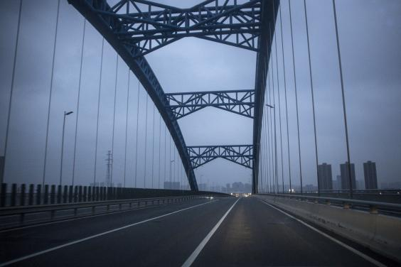 Roads in Wuhan lie empty after authorities imposed travel bans on the city and surrounding area (Getty Images)
