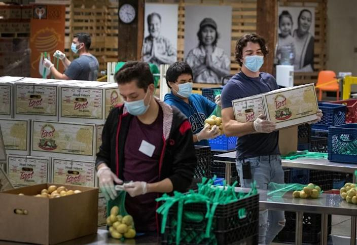IRVINE, CA -- WEDNESDAY, APRIL 1, 2020: Jose Secundino, center in blue sweatshirt, joins fellow recently hired Second Harvest Food Bank of Orange County temporary employees, who have been laid off from restaurant jobs due to the coronavirus pandemic, as they pack boxes of food for the needy. Volunteers then picked up the food and delivered it to local senior centers in Orange County. Photo taken at Second Harvest Food Bank at the Orange County Great Park in Irvine, CA, on April 1, 2020. (Allen J. Schaben / Los Angeles Times)