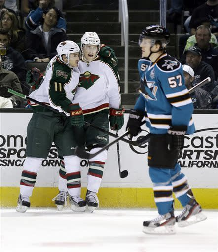 Minnesota Wild's Charlie Coyle, center, celebrates his goal with teammate Zach Parise (11) as San Jose Sharks' Tommy Wingels (57) skates past during the second period of an NHL hockey game in San Jose, Calif., Wednesday, April 3, 2013. (AP Photo/Marcio Jose Sanchez)