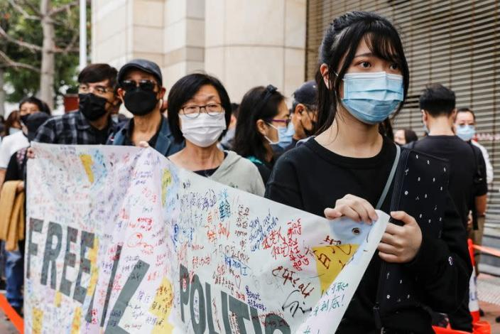 Supporters hold a banner to support pro-democracy activists as they queue up for a court hearing over the national security law outside West Kowloon Magistrates' Courts, in Hong Kong