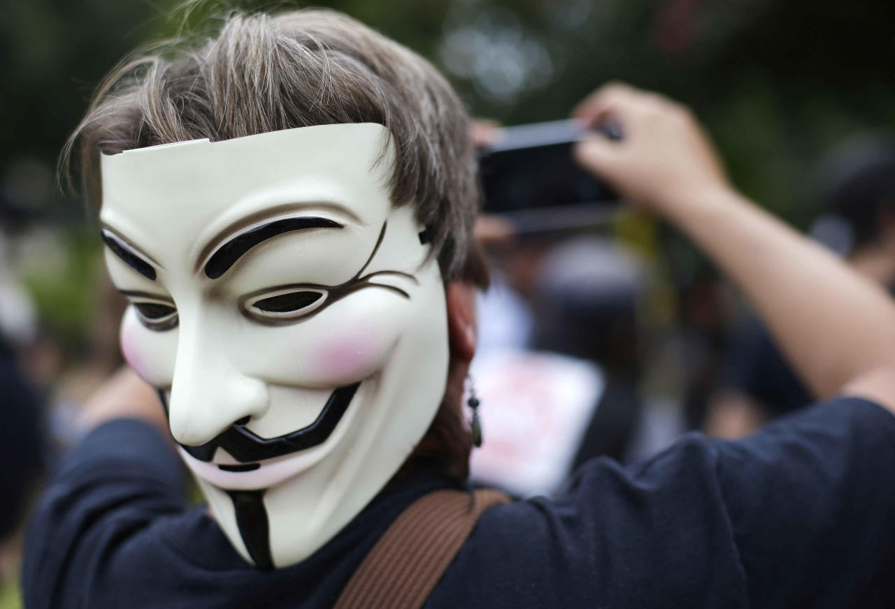 An Occupy demonstrator wearing a Guy Fawkes mask takes a photo of others on a protest march, Tuesday, Sept. 4, 2012, in Charlotte, N.C. The Democratic National Convention begins today. (AP Photo/Patrick Semansky)