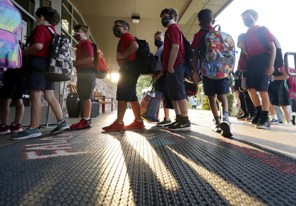 Wearing masks to prevent the spread of COVID-19, elementary school students line up to enter school for the first day of classes in Richardson, Texas, Tuesday, Aug. 17, 2021. Despite Texas Gov Greg Abbott's executive order banning mask mandates by local officials, the Richardson Independent School District and many others across the state are requiring masks for students. (AP Photo/LM Otero)