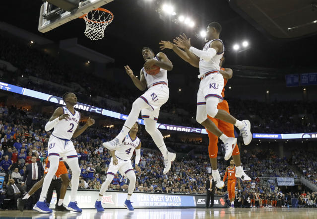 Kansas' Silvio De Sousa pulls down a rebound during the first half of a regional semifinal game against Clemson in the NCAA men's college basketball tournament Friday, March 23, 2018, in Omaha, Neb. (AP Photo/Charlie Neibergall)