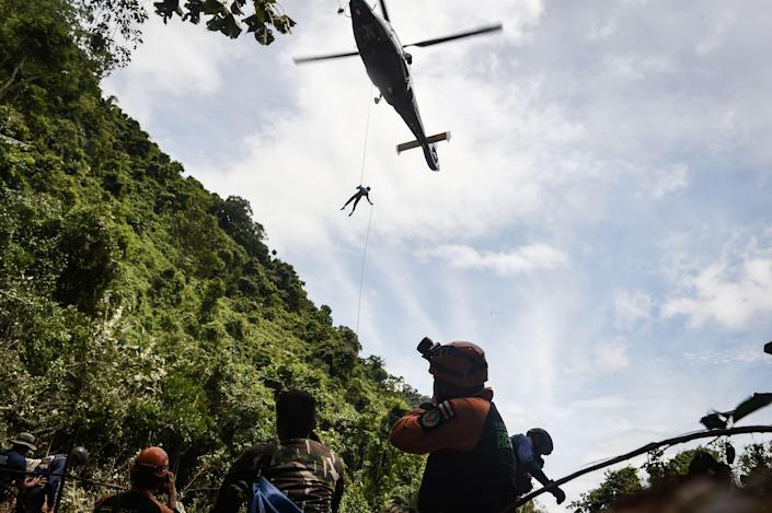 <p>A Thai air force worker drops by helicopter into a clearing in the forest near a possible aboveground opening to the Tham Luang Cave in Chiang Rai Province on June 30, 2018 as the rescue operation continues for the children on a soccer team and their coach. (Photo:Lillian Suwanrumpha/AFP/Getty Images) </p>