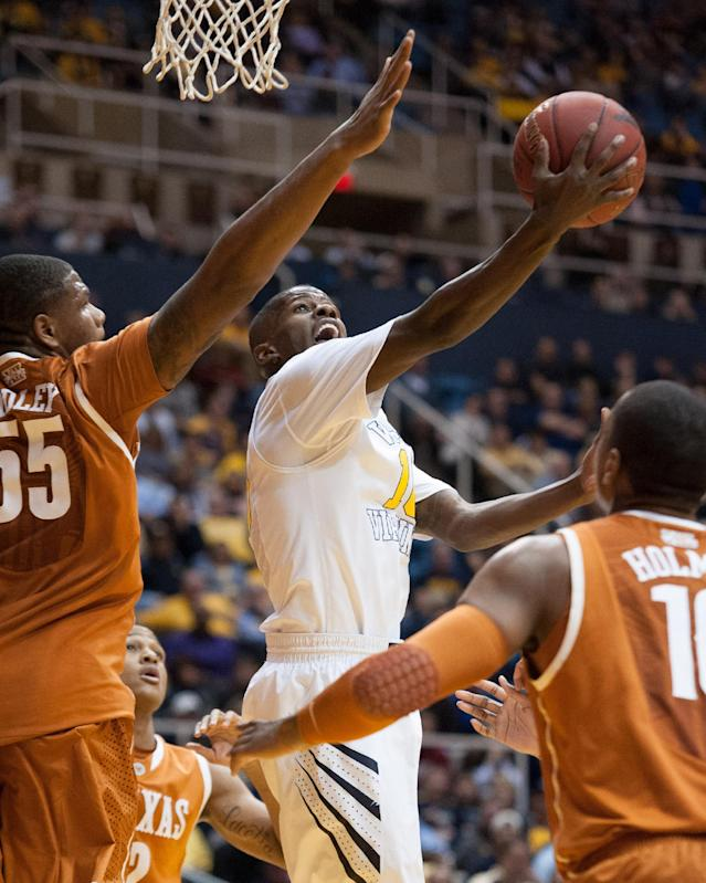 West Virginia's Eron Harris, center, drives to the basket between Texas' defenders during the second half of an NCAA college basketball game Monday, Jan. 13, 2014, in Morgantown, W.Va. Texas won 80-69. (AP Photo/Andrew Ferguson)