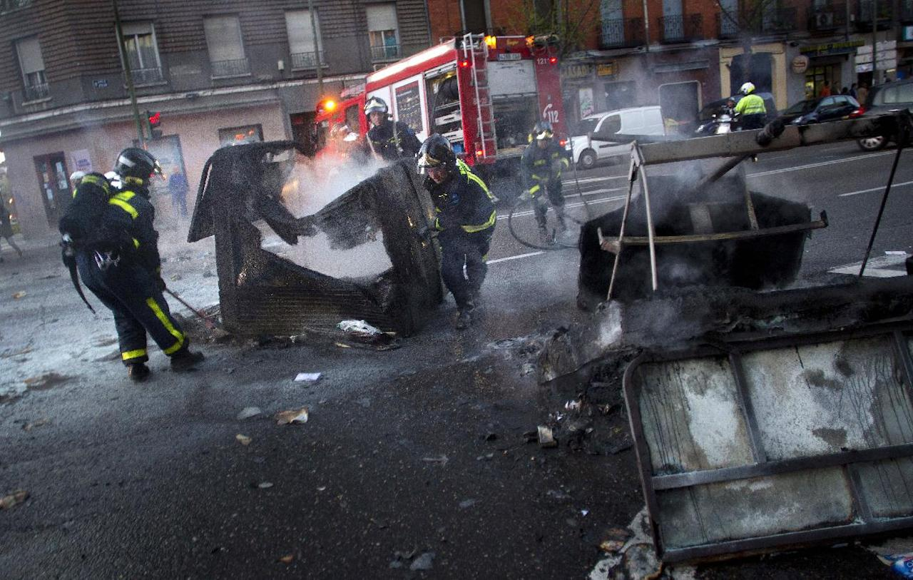 Firemen remove a garbage container that was set on fire during a general strike in Madrid, Spain, Thursday, March 29, 2012. The one-day trade union sponsored general strike is protesting changes to labor market rules long regarded as among Europe's most rigid that include making it cheaper and easier for companies to lay people off and cutting wages. (AP Photo/Alberto Di Lolli)