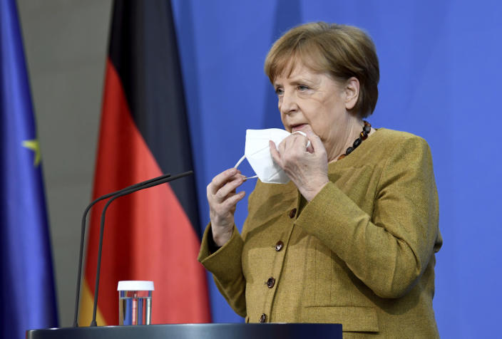German Chancellor Angela Merkel takes off her mask as she arrives to hold a news conference following a virtual summit meeting with G7 leaders at the Chancellery in Berlin, Germany, Friday Feb. 19, 2021. Britain's Prime Minister Boris Johnson chaired a virtual meeting Friday with leaders of the Group of Seven economic world powers, holding their first meeting of 2021. (Annegret Hilse/Pool via AP)