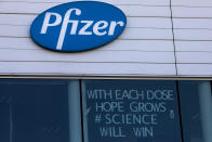 A sign is pasted into an upper window at Pfizer manufacturing center in Puurs, Belgium, Tuesday, Feb. 23, 2021. Two U.K. studies released Monday showed that COVID-19 vaccination programs are contributing to a sharp drop in hospitalizations, boosting hopes that the shots will work as well in the real world as they have in carefully controlled studies. (AP Photo/Virginia Mayo)
