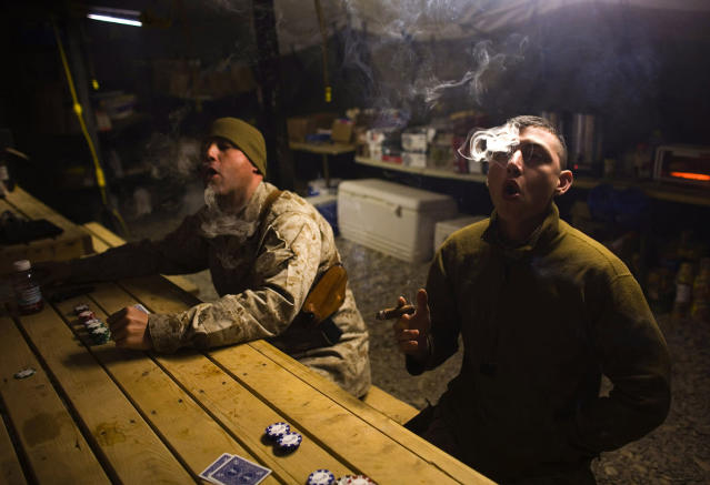 <p>U.S. Marines from MP Company, 1st Marine Division attached to 3rd Battalion 4th Marines, smoke cigars as they play cards at AHP station in Nimroz province, southern Afghanistan, on Jan. 14, 2010. (Photo: Marko Djurica/Reuters) </p>