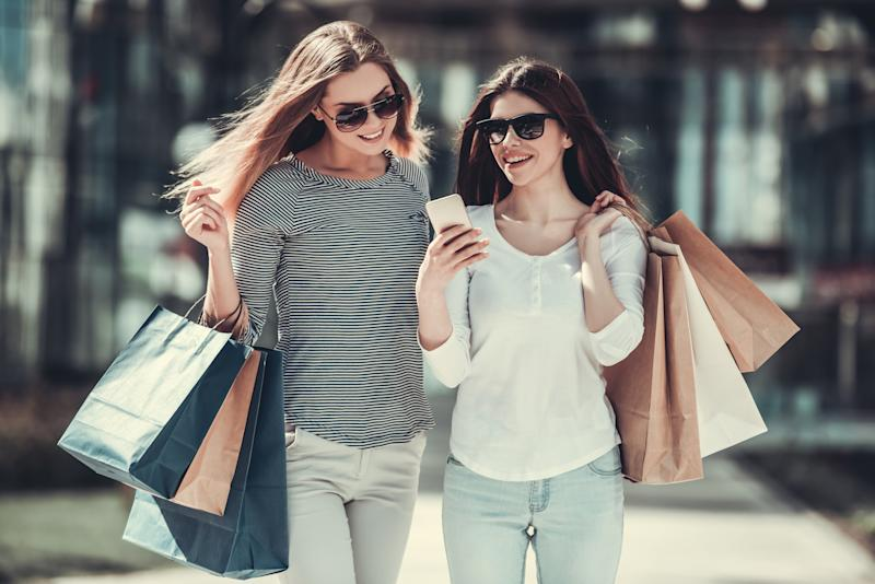 Smiling women wearing sunglasses and carrying shopping bags.
