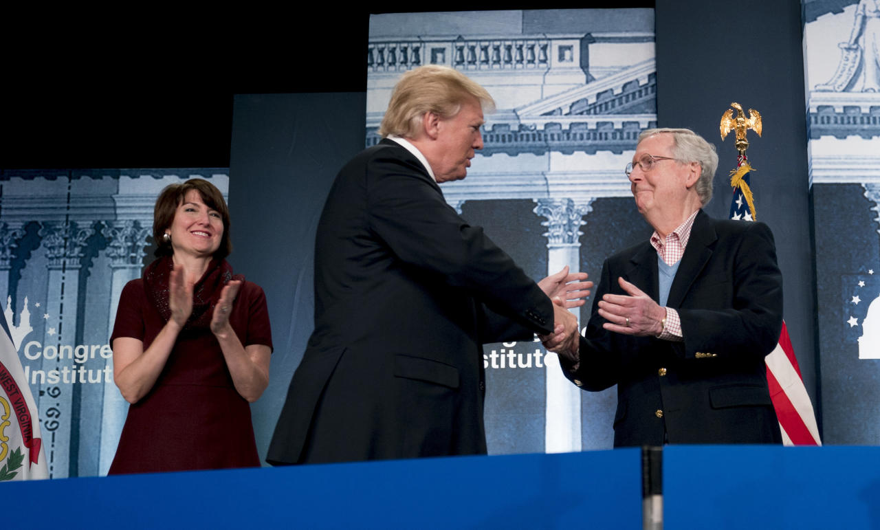 FILE - In this Feb. 1, 2018 file photo, Rep. Cathy McMorris Rodgers, R-Wash., left, watches as President Donald Trump greets Senate Majority Leader Mitch McConnell of Ky., right, at the 2018 House and Senate Republican Member Conference, in White Sulphur Springs, W.Va. Trump's unwillingness to release his tax returns is helping renew a debate on whether the practice should be expected of elected federal office holders ahead of this year's midterms, and in April, 2018, in Washington state's 5th District, McMorris Rodgers, the incumbent who is being challenged by Democrat Lisa Brown, released her returns for the first time since winning the House seat in 2004. (AP Photo/Andrew Harnik, file)