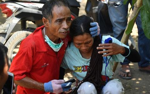 An Indonesian man tries to calm a woman shortly after an aftershock hits the area in Tanjung on Lombok island on August 9  - Credit: ADEK BERRY/AFP