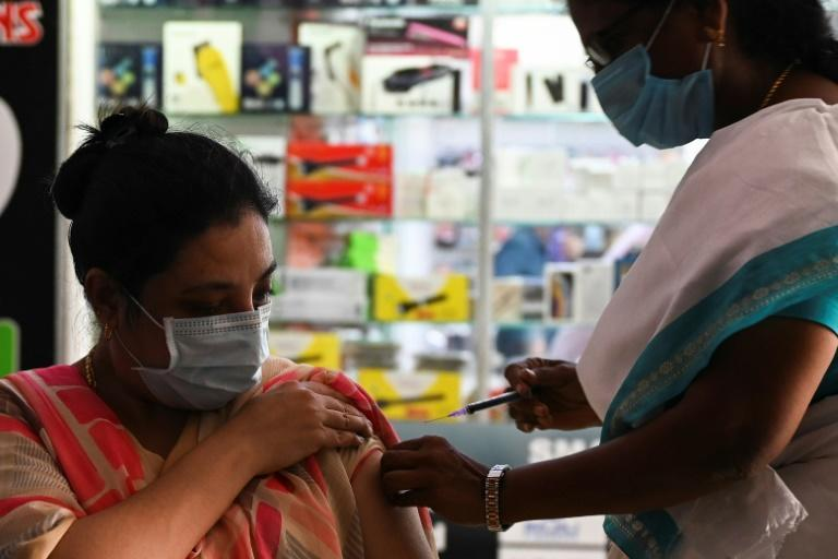 A health worker inoculates a woman with a dose of the Covishield vaccine against the coronavirus at a vaccination camp held at shopping complex in Chennai - India made a record 22 million jabs in a single day (AFP/Arun SANKAR)