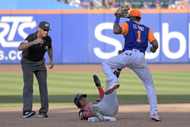 New York Mets shortstop Amed Rosario (1) looks on as umpire Paul Nauert, left, signals Washington Nationals' Juan Soto out while attempting to stretch a single into a double during the eighth inning of a baseball game Saturday, Aug. 25, 2018 in New York. (AP Photo/Bill Kostroun)