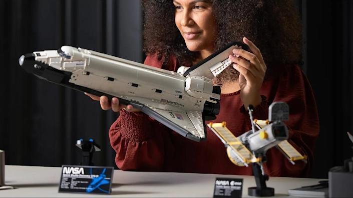 A grown adult woman holds a LEGO space shuttle. On the desk are little NASA placards an a LEGO satellite on a stand.