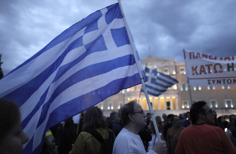 Protesters hold a Greek flag during a demo in front of the parliament in Athens on Wednesday Nov. 7, 2012. Greece's fragile coalition government faces its toughest test so far when lawmakers vote later Wednesday on new painful austerity measures demanded to keep the country afloat, on the second day of a nationwide general strike. The euro13.5 billion ($17.3 billion) package is expected to scrape through Parliament, following a hasty one-day debate. But potential defections could severely weaken the conservative-led coalition formed in June with the intention of keeping Greece in the euro.(AP Photo/Petros Giannakouris)