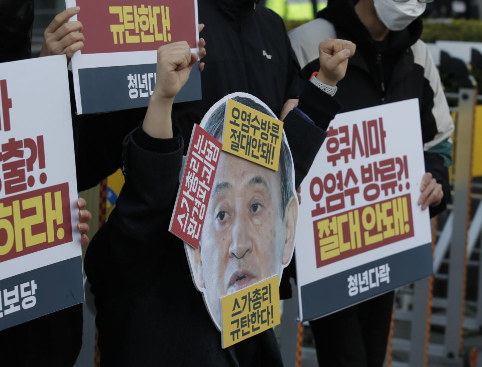"A member of youth groups wearing a cutout of Japanese Prime Minister Yoshihide Suga performs to denounce the Japan government's decision on Fukushima water, in Seoul, South Korea, Tuesday, April 13, 2021. Japan's government decided Tuesday to start releasing massive amounts of treated radioactive water from the wrecked Fukushima nuclear plant into the Pacific Ocean in two years - an option fiercely opposed by local fishermen and residents. The Korean letters read: ""Denounce Prime Minister Yoshihide Suga."" (AP Photo/Lee Jin-man)"