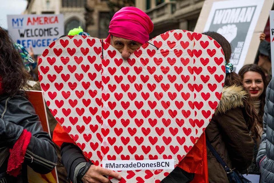 <p>While the women's march originated in Washington, D.C., people gathered together all around the world. This man demonstrated in Spain, wearing a pink hat and carrying a heart-shaped poster. (Photo: Getty Images) </p>