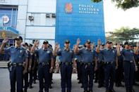 Policemen swear allegiance to the Philippine Constitution during a flag-raising ceremony at the grounds of Station 6, Batasan Police Station, in Quezon City, Metro Manila, Philippines December 4, 2017. REUTERS/Erik De Castro