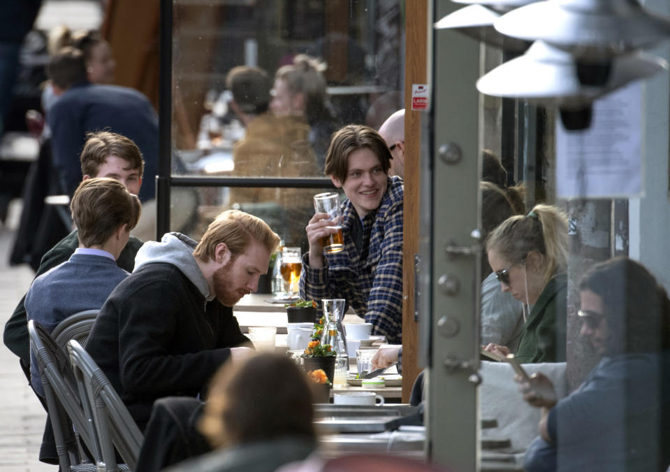 People enjoy themselves at an outdoor restaurant, amid the coronavirus outbreak, in central Stockholm, Sweden, Monday April 20, 2020. (Anders Wiklund/TT News Agency via AP)