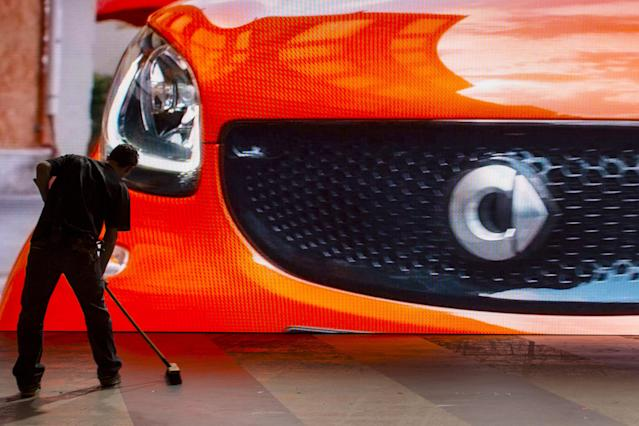 A smart car is seen on a screen while a worker sweeps the stage before the Mercedes-Benz & smart Media Night at the 2015 New York International Auto Show in New York March 31, 2015. REUTERS/Andrew Kelly