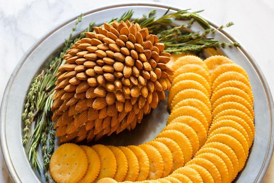 """<p>This impressive pinecone-inspired cheese ball is surprisingly easy to make. With just five ingredients and only 20 minutes of prep, it couldn't be easier. </p><p><a href=""""https://www.thepioneerwoman.com/food-cooking/recipes/a81851/holiday-cheese-ball/"""" rel=""""nofollow noopener"""" target=""""_blank"""" data-ylk=""""slk:Get the recipe."""" class=""""link rapid-noclick-resp""""><strong>Get the recipe.</strong></a></p>"""