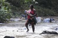 A migrant woman crosses the Acandi River with a child in her arms, in Acandi, Colombia, Wednesday, Sept. 15, 2021. A group of migrants, following a well-beaten, multi-nation journey towards the U.S., will continue their journey through a jungle known as the Darien Gap. (AP Photo/Fernando Vergara)