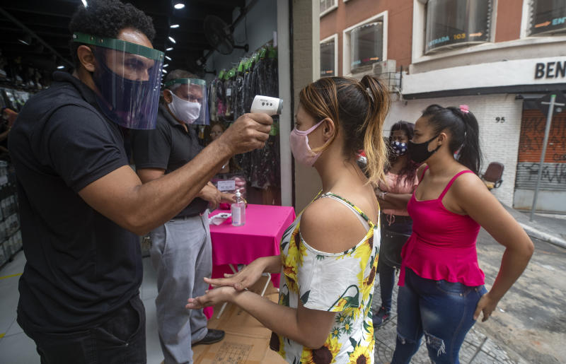 A mask-wearing shopper gets her temperature checked before entering a store in a downtown shopping district in Sao Paulo, Brazil, Wednesday, June 10, 2020. Retail shops reopened on Wednesday in Brazil's biggest city after a two-month coronavirus pandemic shutdown aimed at containing the spread of the new coronavirus. (AP Photo/Andre Penner)