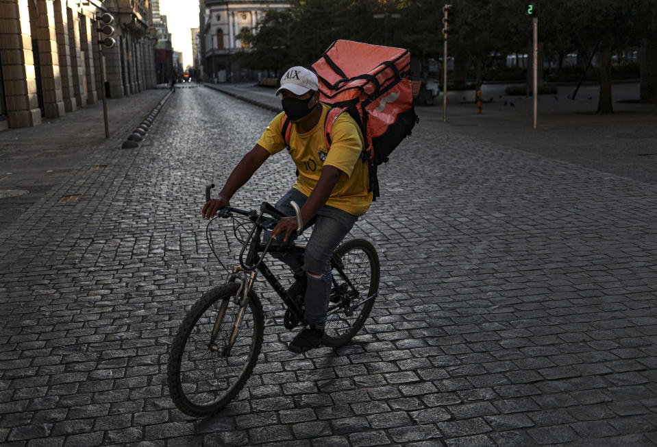 A delivery food bicyclist rides through a deserted street during a reinstated lockdown to help contain the spread of COVID-19, in Santiago, Chile, Saturday, March 27, 2021. (AP Photo/Esteban Felix)