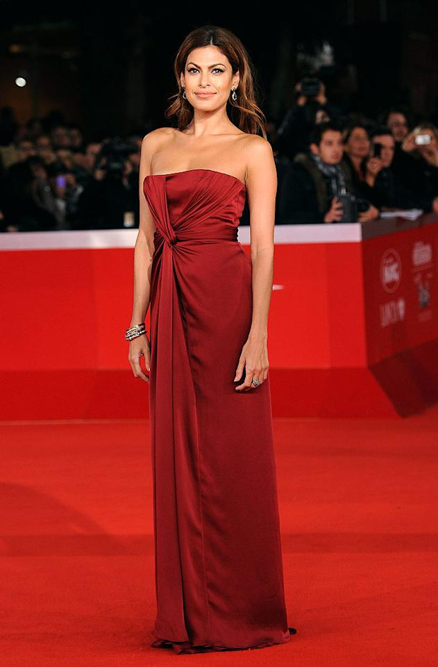 "Eva Mendes rocked the red carpet at the re-release of ""La Dolce Vita"" during the 5th International Rome Film Festival in a ruby-colored Gucci gown, which featured a tantalizingly twisted bodice. Tasteful jewels and muted makeup completed her flawless look. Venturelli/<a href=""http://www.wireimage.com"" target=""new"">WireImage.com</a> - October 30, 2010"