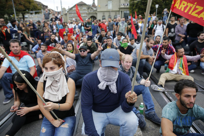 FILE - In this Saturday, Sept. 12, 2015 file photo, Kurds living in Switzerland stage a protest on the Kirchenfeld bridge after clashes with Turkish nationalists in downtown Bern, Switzerland. At a time when seemingly everyone in Europe is wearing masks to battle COVID-19, the Swiss go to the polls Sunday, March 7, 2021 to vote on a long-laid proposal to ban face-coverings like niqabs and burqas worn by some Muslim women or by protesters in ski masks or bandannas. (Peter Klaunzer/Keystone via AP, File)