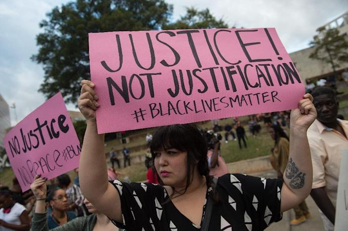 Protesters hold up signs during a demonstration against police brutality in Charlotte, North Carolina, on September 21, 2016 (AFP Photo/Nicholas Kamm)
