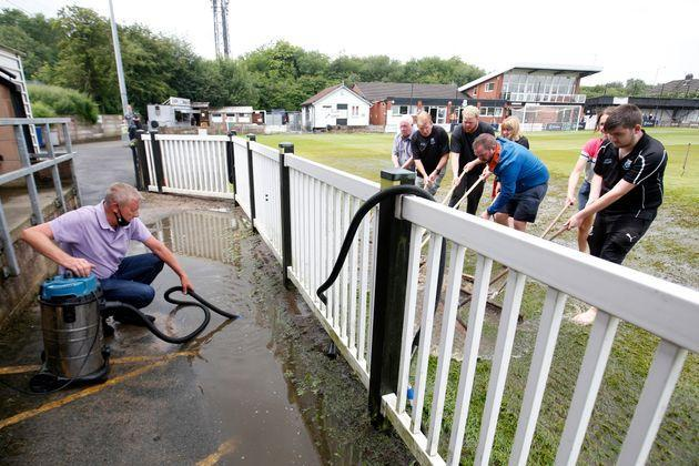 Staff work on a waterlogged pitch before a cricket game at Sir Tom Finney Stadium in Blackburn on July 10 (Photo: Ed Sykes - CameraSport via Getty Images)
