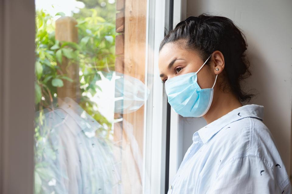 Young hispanic woman, wearing protective face mask, standing by the window and looking out to the street in times of coronavirus crisis, staying at home