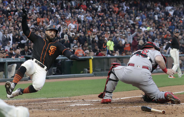 San Francisco Giants' Kevin Pillar, left, slides past Cincinnati Reds catcher Tucker Barnhart to score a run during the fourth inning of a baseball game in San Francisco, Saturday, May 11, 2019. (AP Photo/Jeff Chiu)