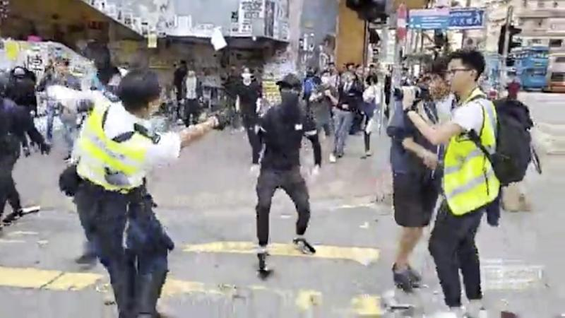 In an image from video a police officer, left, prepares to shoot a protester, centre, in Hong Kong