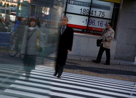 People walk past an electronic board showing stock prices outside a brokerage at a business district in Tokyo, Japan, January 23, 2017.  REUTERS/Kim Kyung-Hoon