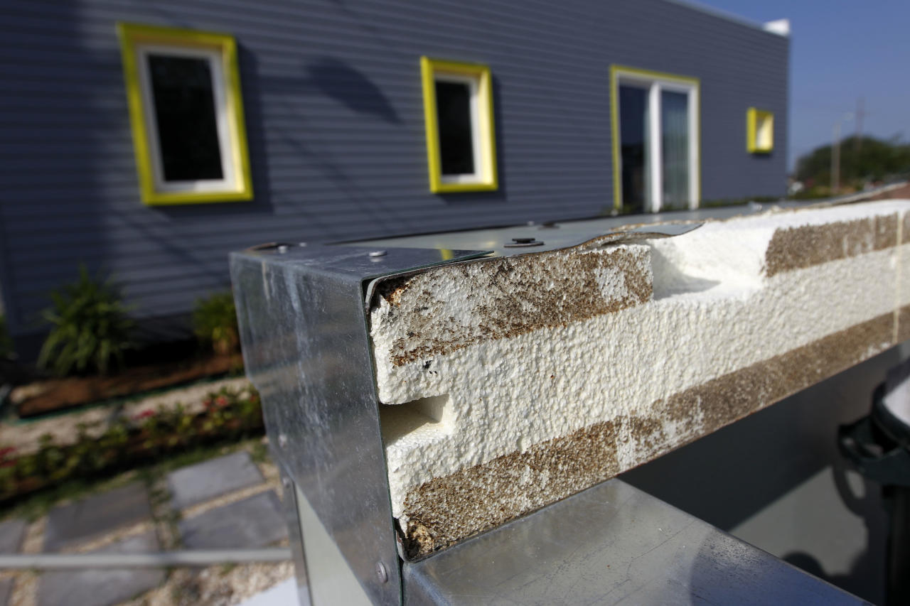 ADVANCE FOR WEEKEND EDITIONS APRIL 21-22 - In a Thursday, April 5, 2012 photo, a sample cross section of a wall built with an SIP eps foam core encased in a Galvalume steel skin is seen behind the Roese Sunshower SSIP house in New Orleans. The house is meant to go up quickly after disasters and then serve as permanent housing that can withstand future calamities. It's designed to be environmentally friendly, survive outside damaged utility grids and can be shipped in pieces in a single container and assembled like an erector set. (AP Photo/Gerald Herbert)
