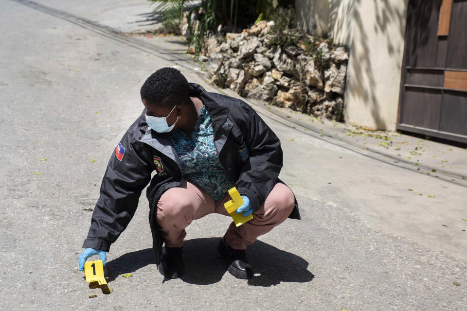 An investigator places an evidence marker next to a bullet casing outside the residence of Haitian President Jovenel Moise, in Port-au-Prince, Haiti, Wednesday, July 7, 2021. Gunmen assassinated Moise and wounded his wife in their home early Wednesday. (AP Photo/Joseph Odelyn)