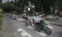 Wilson Guzman, a tour guide, right, leads an electric wheelchair tour in Medellin, Colombia, Wednesday, Nov. 18, 2020. For the equivalent of $25, both people who can and can't walk can get on the electric wheelchairs and take the three-hour tour of the city's riverside parks, which includes stops at a coffee shop and a bar that does beer tasting. (AP Photo/Fernando Vergara)