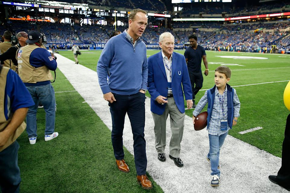Former Colts quarterback Peyton Manning walks on the sidelines with his son Marshall Manning (right) and former GM Bill Polian (middle) before a game.